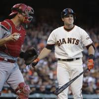 Photo - San Francisco Giants' Adam Duvall, right, reacts after striking out on a foul tip as Cincinnati Reds catcher Devin Mesoraco, left, looks on in the second inning of their baseball game Thursday, June 26, 2014, in San Francisco. Duvall was making his major league debut in the game. (AP Photo/Eric Risberg)