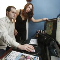 Photo - Matias Menis and Diana Miller work on their Spanish language sports magazine from their home in Norman, OK, Friday, March 11, 2011. By Paul Hellstern, The Oklahoman