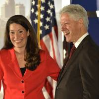 Photo - Democratic Senate challenger Alison Lundergan Grimes left, speaks with former Presidet Bill Clinton as they are introduced at a fundraiser at the Galt House Hotel, Tuesday, Feb. 25, 2014, in Louisville, Ky. (AP Photo/Timothy D. Easley)