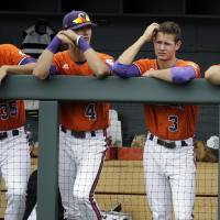 Photo - Clemson's Mike Triller (35), Eli White (4), Tyler Krieger (3) and Shane Kennedy (11) watch during the top of the ninth inning of their 18-1 loss to Oregon in an NCAA college baseball regional tournament game on Friday, May 30, 2014, in Nashville, Tenn. (AP Photo/Mark Humphrey)