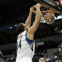 Photo -   Maccabi Haifa's Pat Calathes, right, looks on as Minnesota Timberwolves' Nikola Pekovic, of Montenegro, dunks during the first half of an NBA exhibition basketball game against the Israeli team, Tuesday, Oct. 16, 2012, in Minneapolis. (AP Photo/Jim Mone)