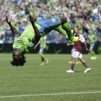 Photo - Seattle Sounders' Obafemi Martins does a backflip after he scored a goal against the Colorado Rapids, Saturday, April 26, 2014, in the second half of an MLS soccer match in Seattle. The Sounders defeated the Rapids 4-1. (AP Photo/Ted S. Warren)
