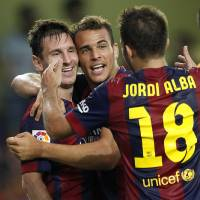 Photo - Barcelona's Sandro, center, is congratulated by teammate Lionel Messi, from Argentina, left, after scoring a goal against Villarreal during a Spanish La Liga soccer match at the Madrigal stadium in Villarreal, Spain, on Sunday, Aug 31, 2014.(AP Photo/Alberto Saiz)