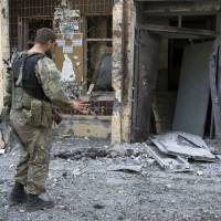 Photo - A pro-Russian fighter gestures near a body of a community service worker who was killed during the shelling outside a residential apartment house in Donetsk, eastern Ukraine Tuesday, July 29, 2014.  Local residents said it was a shelling from direction of Ukrainian army's positions. (AP Photo/Dmitry Lovetsky)
