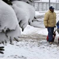 Photo - People walk in the snow at Buffalo Niagara International Airport in Buffalo, N.Y., Saturday, Dec. 29, 2012. A mild but widespread winter storm has developed over the Northeast and the upper Ohio River Valley, the second in less than a week for the regions. (AP Photo/Mel Evans)