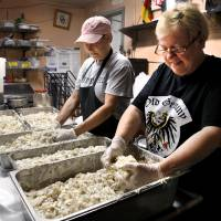 Photo -  Women use their hands to mix dressing and spices into sliced potatoes to make German potato salad in the kitchen of Old Germany Restaurant.  Photo by Jim Beckel, The Oklahoman   Jim Beckel -