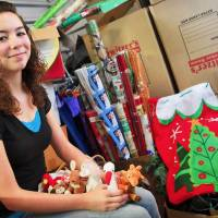 """Photo - Mariah McClellin of Oklahoma City sits in a storage unit that houses donations for """"Stockings for the Homeless,"""" a holiday program she founded several years ago. The stockings contain donations such as holiday gifts, such as the Beanie Babies at left, or toiletry items.  Photos By Chris Landsberger, The Oklahoman"""