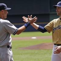 Photo - New York Yankees Derek Jeter greets Milwaukee Brewers' Ryan Braun  before their game against the Milwaukee Brewers Sunday, May 11, 2014, in Milwaukee. It will be Jeter's last game at Miller park. (AP Photo/Jeffrey Phelps)