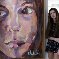 """Photo - In this Thursday, Aug. 14, 2014 photo, Isabella Rose Taylor, 13, poses with her art work and clothing designs at her home, in Austin, Texas. Her fashion line is debuting at Nordstrom stores and she's set to hold her first show at New York Fashion Week. Taylor said she created a fall line with a """"street grunge vibe"""" and """"modern hippie"""" inspiration. (AP Photo/Eric Gay)"""