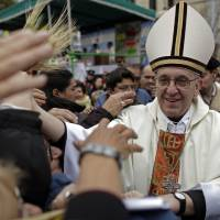 Photo - In this August 2009 photo, Argentina's Cardinal Jorge Bergoglio, right, greets faithful outside the San Cayetano church in Buenos Aires, Argentina. On Wednesday, Bergoglio was elected pope.  Natacha Pisarenko - ASSOCIATED PRESS