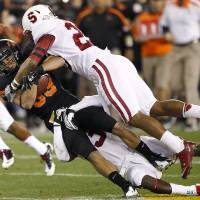 Photo - Oklahoma State wide receiver Colton Chelf, left, is tackled by Stanford safety Delano Howell, right, during the first half of the Fiesta Bowl NCAA college football game Monday, Jan. 2, 2012, in Glendale, Ariz. (AP Photo/Matt York)  ORG XMIT: PNP121