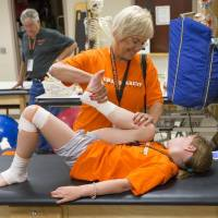 Photo - A youngster and grandmother work through sports injuries as part of Grandparent University at OSU. Image from University Marketing/Oklahoma State University