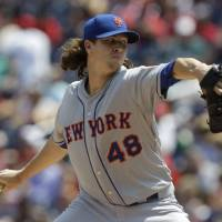 Photo - New York Mets pitcher Jacob deGrom throws against the Washington Natinals during the first inning of a baseball game, Thursday, Aug. 7, 2014, in Washington. (AP Photo/Luis M. Alvarez)