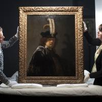 Photo - This undated handout photo provided by the National Trust shows Tina Sitwell, Paintings conservation advisor, left, and Patricia Pertnyk, House Steward, holding the self-portrait of Rembrandt which has returned to Buckland Abbey, Devon, England.  Scientific tests have confirmed that a painting donated to Britain's National Trust by a wealthy supporter is a Rembrandt self-portrait worth tens of millions of pounds (dollars). The painting was given to the heritage body in 2010 and hangs in Buckland Abbey in southwest England, former home of 16th-century seafarer Francis Drake. (AP Photo/ Steven Haywood/National Trust, PA) UNITED KINGDOM OUT