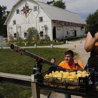 Ethan Kenoyer, 17, fires the corn cannon with Erin Howell-Conner looking on at Howell's, which charges $2 to fire four shots. PHOTO: RACHEL MUMMEY FOR THE WALL STREET JOURNAL