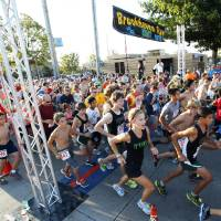 Photo - More than 1,200 runners take to the streets Saturday as the Brookhaven Run gets under way.