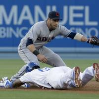 Photo - Cleveland Indians second baseman Jason Kipnis, top, fails to catch the throw as Los Angeles Dodgers' Yasiel Puig slides into second base for a double during the first inning of a baseball game in Los Angeles, Tuesday, July 1, 2014. (AP Photo/Chris Carlson)