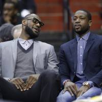 Photo - Miami Heat's LeBron James, left, and Dwyane Wade sit on the bench during the first half of an NBA basketball game against the Washington Wizards on Wednesday, April 10, 2013, in Washington. (AP Photo/Evan Vucci)