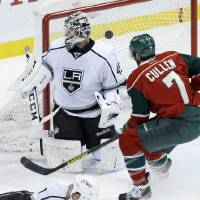 Photo - Minnesota Wild center Matt Cullen (7) watches as a shot by teammate Cal Clutterbuck makes it past Los Angeles Kings goalie Jonathan Bernier (45) during the first period of an NHL hockey game in St. Paul, Minn., Tuesday, April 23, 2013. (AP Photo/Ann Heisenfelt)