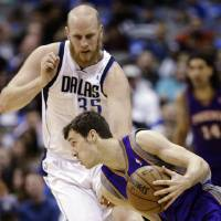 Photo - Phoenix Suns guard Goran Dragic (1), of Slovenia, drives against Dallas Mavericks center Chris Kaman (35) during the first half of an NBA basketball game, Wednesday, April 10, 2013, in Dallas. (AP Photo/LM Otero)