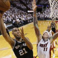 Photo - San Antonio Spurs power forward Tim Duncan (21) shoots against Miami Heat power forward Chris Andersen (11) during the first half of Game 1 of basketball's NBA Finals, Thursday, June 6, 2013 in Miami. (AP Photo/Mike Ehrmann, Pool)