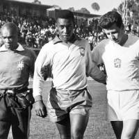 Photo - CORRECTS YEAR OF CHILE WORLD CUP TO 1962 - FILE - This February 1962 file photo, shows Edson Arantes do Nascimento known as Pele, center, trainer Mario Americo, left, and Czech player Masopust. After Neymar's injury in this 2014 Soccer World Cup while playing against Colombia, Brazil remembers when Pele, its best player in the Chile 1962 World Cup was also sidelined because of injury in the tournament, and Brazil still won the title. (AP Photo/File)