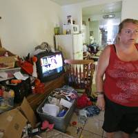 Photo - In this Tuesday, April 8, 2014 photo, Theresa Muller prepares to move out of her motel room she shares with her boyfriend, father and three children in Kissimmee, Fla.   Muller and her family have been homeless but plan to move to a home in a neighboring county. (AP Photo/John Raoux)