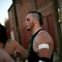 """Photo -  Brandan Bulmer, who wrestles under the name """"Drake Gallows"""" talks with other wreslters including Eric Torres (left) who wrestles under the name """"Rick Russo"""" critque their show and plan the next match during a show by members of Sooner World Class Wrestling at the historic Yale Theater in the Capitol Hill neighborhood in south Oklahoma City on Saturday, July 23, 2011. Bulmer's brother Dallas Bulmer, who wrestled under the name Crisstopher """"The Freakshow"""" Crow, died in a car accident on June 22, 2011. Saturday's show was the third of three tribute shows dedicated to Bulmer. Photo by John Clanton, The Oklahoman"""