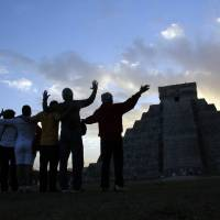 Photo - People gesture toward the the Kukulkan temple in Chichen Itza, Mexico, Friday, Dec. 21, 2012. Ceremonial fires burned and conches sounded off as dawn broke over the steps of the main pyramid at the Mayan ruins of Chichen Itza Friday, making what many believe is the conclusion of a vast, 5,125-year cycle in the Mayan calendar. Some have interpreted the prophetic moment as the end of the world. The hundreds gathered in the ancient Mayan city, however, said they believed it marked the birth of a new and better age. (AP Photo/Israel Leal)