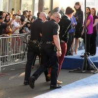 Photo - A fan is walked off carpet in handcuffs after allegedly attacking Brad Pitt at the world premiere of