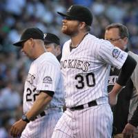 Photo - Colorado Rockies starting pitcher Brett Anderson (30) holds his back as he leaves a game against the Chicago Cubs in the fourth inning of a baseball game in Denver on Tuesday, Aug. 5, 2014.Rockies manager Walt Weiss (22) talks to home plate umpire umpire Marty Foster.(AP Photo/Joe Mahoney)