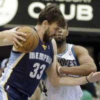Photo - Memphis Grizzlies' Marc Gasol, left, of Spain, makes his way past Minnesota Timberwolves' Derrick Williams in the first quarter of an NBA basketball game on Saturday, March 30, 2013, in Minneapolis. (AP Photo/Jim Mone)