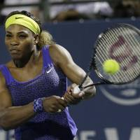 Photo - Serena Williams returns the ball to Ana Ivanovic, from Serbia, during the second set of their match in the Bank of the West Classic tennis tournament in Stanford, Calif., Friday, Aug. 1, 2014. Williams won 2-6, 6-3, 7-5. (AP Photo/Jeff Chiu)