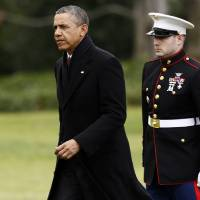 Photo - President Barack Obama walks past a Marine honor guard as he steps off the Marine One helicopter and walks on the South Lawn at the White House in Washington, Thursday, Dec. 27, 2012, as he returned early from his Hawaii vacation for meetings on the fiscal cliff. (AP Photo/Charles Dharapak)
