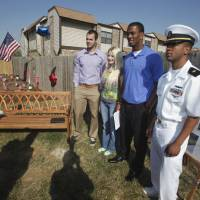 Photo - DEDICATE / DEDICATED / SPC. JASON HUNT: Landry Jones and Julian Wilson, University of Oklahoma football players; stand with Jennifer Hunt, widow of Spc. Jason D. Hunt; and Navy officer candidate James Smith at the dedication of Quinton Carter's charity educational garden at KinderCare on Friday, March 25, 2011, in Norman, Okla.   Photo by Steve Sisney, The Oklahoman