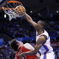 Photo -  Oklahoma City Thunder guard Russell Westbrook, right, dunks over Chicago Bulls center Omer Asik, left, in the third quarter of an NBA basketball game in Oklahoma City, Sunday, April 1, 2012. (AP Photo/Sue Ogrocki)
