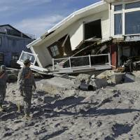 Photo - National Guardsmen Specialist Ivan Pimentel, left, and PFC Harry Cadet walk along the beach past a destroyed house during a break in their work in the Rockaways, Thursday, Jan. 10, 2013, in New York.  The guardsmen said they were working with the New York City Office of Emergency Management going door-to-door to determine if residents needed portable heaters or other items to in the wake of Superstorm Sandy. Using portable personal tablets, they said they could provide residents with a heater within 30 minutes. (AP Photo/Kathy Willens)