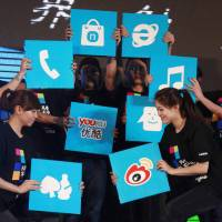 Photo - In this March 28, 2012 photo, Chinese performers hold up cards showing the various apps available for online users for shopping and other services at the launch of a mobile phone in Beijing, China. In an abrupt shift, some 81 percent of China's 618 million Internet users go online via smartphone or tablet, part of a worldwide trend known as the mobile Internet. The services Chinese users flock to are usually privately owned, while the competitors they leave behind belong to the state. Video websites compete with state TV, online financial services draw deposits away from banks and instant messaging apps take revenue from government-owned phone carriers. (AP Photo/Ng Han Guan)