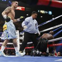 Photo - Marcos Maidana, left, from Argentina, watches after knocking Floyd Mayweather Jr. through the ropes in their WBC-WBA welterweight title boxing fight Saturday, May 3, 2014, in Las Vegas. At center is referee Tony Weeks. (AP Photo/Eric Jamison)