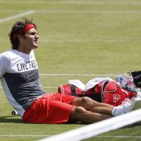 Photo - Roger Federer of Switzerland sits on the court  during a practice session ahead of the All England Lawn Tennis Championships in Wimbledon, London,  Sunday June  22, 2014. The Championships start Monday June 23. (AP Photo/Sang Tan)