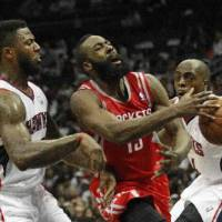 Photo - Houston Rockets shooting guard James Harden,center, is fouled as he drives between Atlanta Hawks shooting guard DeShawn Stevenson (92) and Devin HArris, right, in the second half of an NBA basketball game on Friday, Nov. 2, 2012, in Atlanta. Houston won 109-102. (AP Photo/John Bazemore)