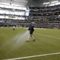 Photo - A grounds crew member waters the turf before the Gold Cup semifinals between the United States and Honduras at Cowboys Stadium, Wednesday, July 24, 2013, in Arlington, Texas. (AP Photo/Brandon Wade)