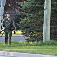 Photo - A heavily armed man that police have identified as Justin Bourque walks on Hildegard Drive in Moncton, New Brunswick, on Wednesday, June 4, 2014, after several shots were fired in the area. The man suspected in the shooting deaths of three Royal Canadian Mounted Police and the wounding of two others in a rare case of gun violence in eastern Canada was arrested early Friday, police said. (AP Photo/The Canadian Press, Moncton Times & Transcript, telegraphjournal.com, Viktor Pivovarov) MANDATORY CREDIT