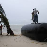 Photo -   Men stand on top of a marine fender that was ripped from a dock after Hurricane Ernesto made landfall overnight in Mahahual, near Chetumal, Mexico, Wednesday, Aug. 8, 2012. (AP Photo/Israel Leal)