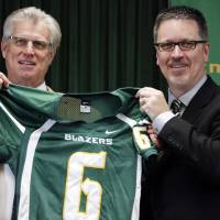 Photo - New Belhaven University football coach, left, and athletic director Scott Little hold up a football jersey after Mumme was introduced during an NAIA college football nbews conference in Jackson, Miss., Tuesday, Jan. 21, 2014. Mumme, a former head coach at a number of programs including Division 1 schools, Kentucky and New Mexico State University, most recently was passing game coordinator at SMU. (AP Photo/Rogelio V. Solis)