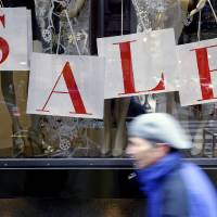 """Photo - In this Tuesday, Dec. 18, 2012, photo, a person passes a retail store with sale sign displayed in the window in Philadelphia. When it comes to big discounts, better late than never. This holiday shopping season, stores haven't been offering the same big discounts as they did in previous years as they tried to lure shoppers in with other incentives,but during the final days leading up to Christmas, shoppers will see more of those jaw-dropping """"70 percent off"""" sale signs as stores try to salvage a season that so far has been disappointing.  (AP Photo/Matt Rourke)"""