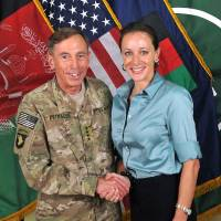 Photo -   This July 13, 2011, photo made available on the International Security Assistance Force's Flickr website shows the former Commander of International Security Assistance Force and U.S. Forces-Afghanistan Gen. Davis Petraeus, left, shaking hands with Paula Broadwell, co-author of