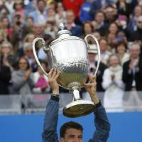 Photo - Grigor Dimitrov of Bulgaria holds up the trophy after his win against Feliciano Lopez of Spain at the end of their Queen's Club grass court championships singles final tennis match in London, Sunday, June 15, 2014. (AP Photo/Sang Tan)