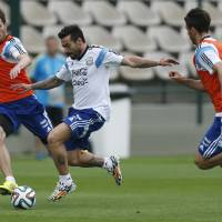 Photo - Argentina's Ezequiel Lavezzi, center, and Jose Maria Basanta, left, vie for the ball as Martin Demichelis, right, looks on during a training session in Vespasiano, near Belo Horizonte, Brazil, Thursday, June 12, 2014. Argentina will play in group F of the Brazil 2014 soccer World Cup. (AP Photo/Victor R. Caivano)