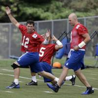 Photo - Indianapolis Colts quarterback Andrew Luck (12), along with fellow quarterbacks Matt Hasselbeck, right, and Chandler Harnish, stretch during practice at the NFL team's football training camp in Anderson, Ind., Sunday, July 28, 2013. (AP Photo/Michael Conroy)